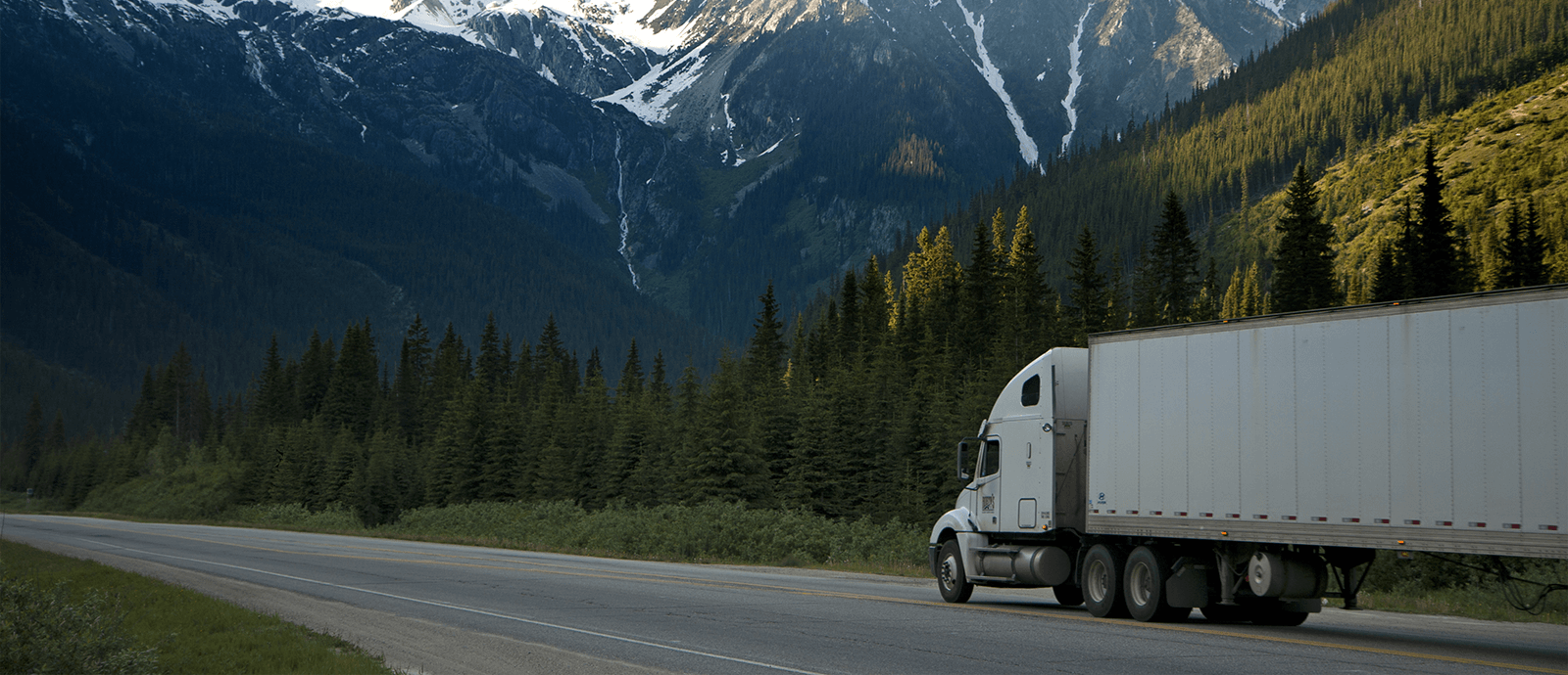 Semi on the road driving through the mountain regions