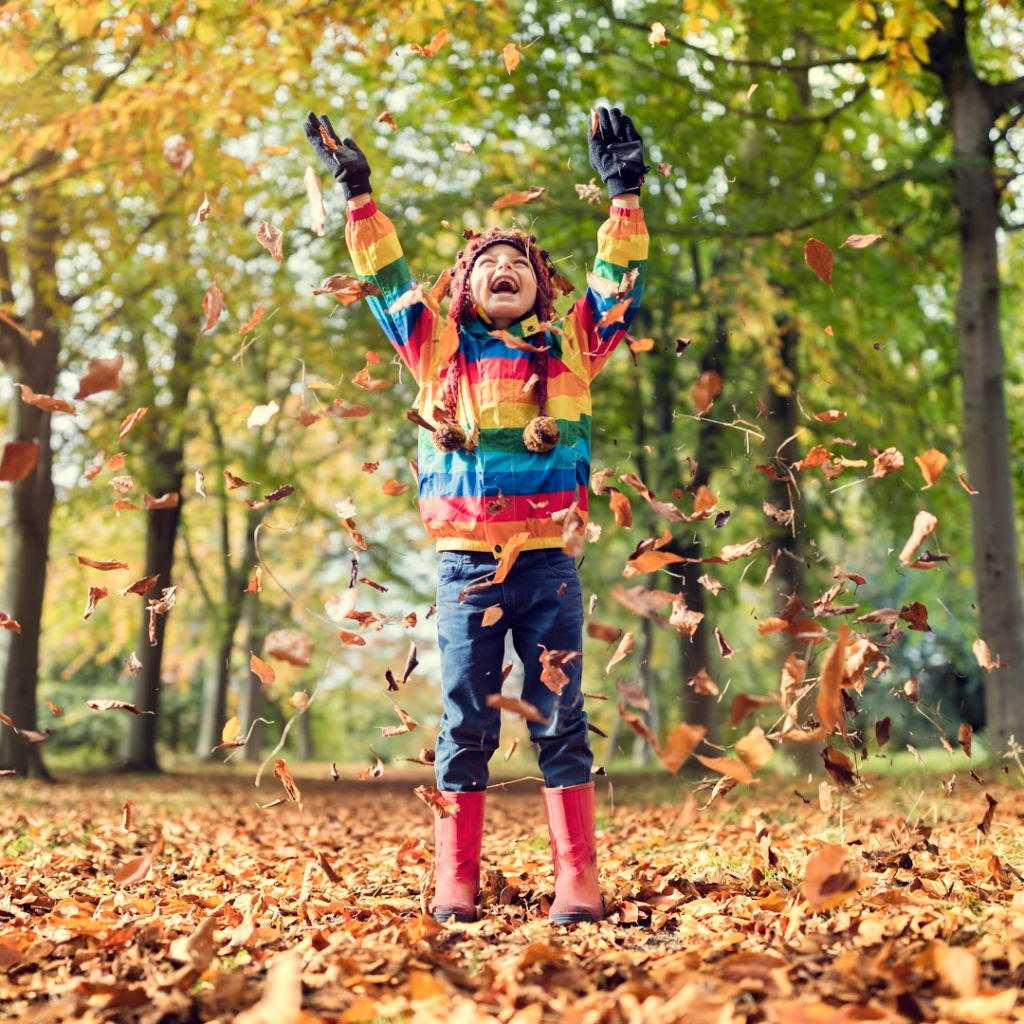 beholdher.life  - child playing in the Autumn Leaves - article about Gratitude and Giving Thanks