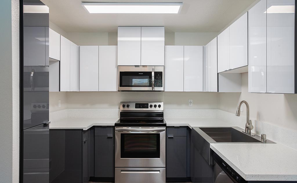 Kitchen with white and gray cabinets and countertops cabi