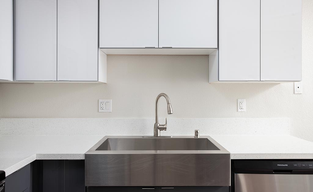 Stainless kitchen sink and white cabinets