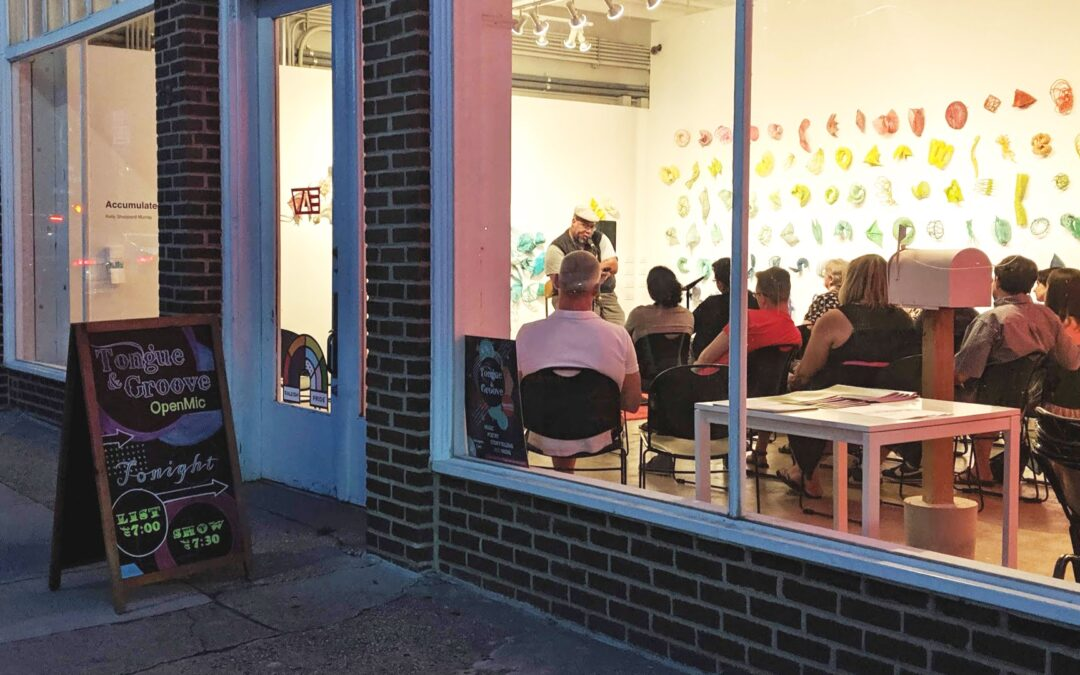 view into the window of an open mic with an attentive audience