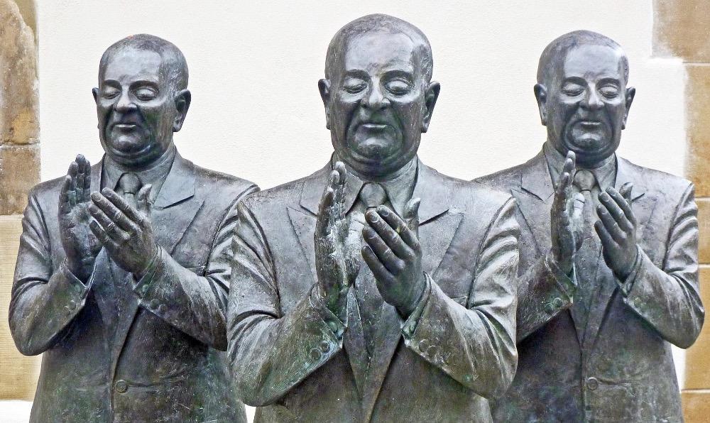 sculpture of 3 dour men applauding awkwardly