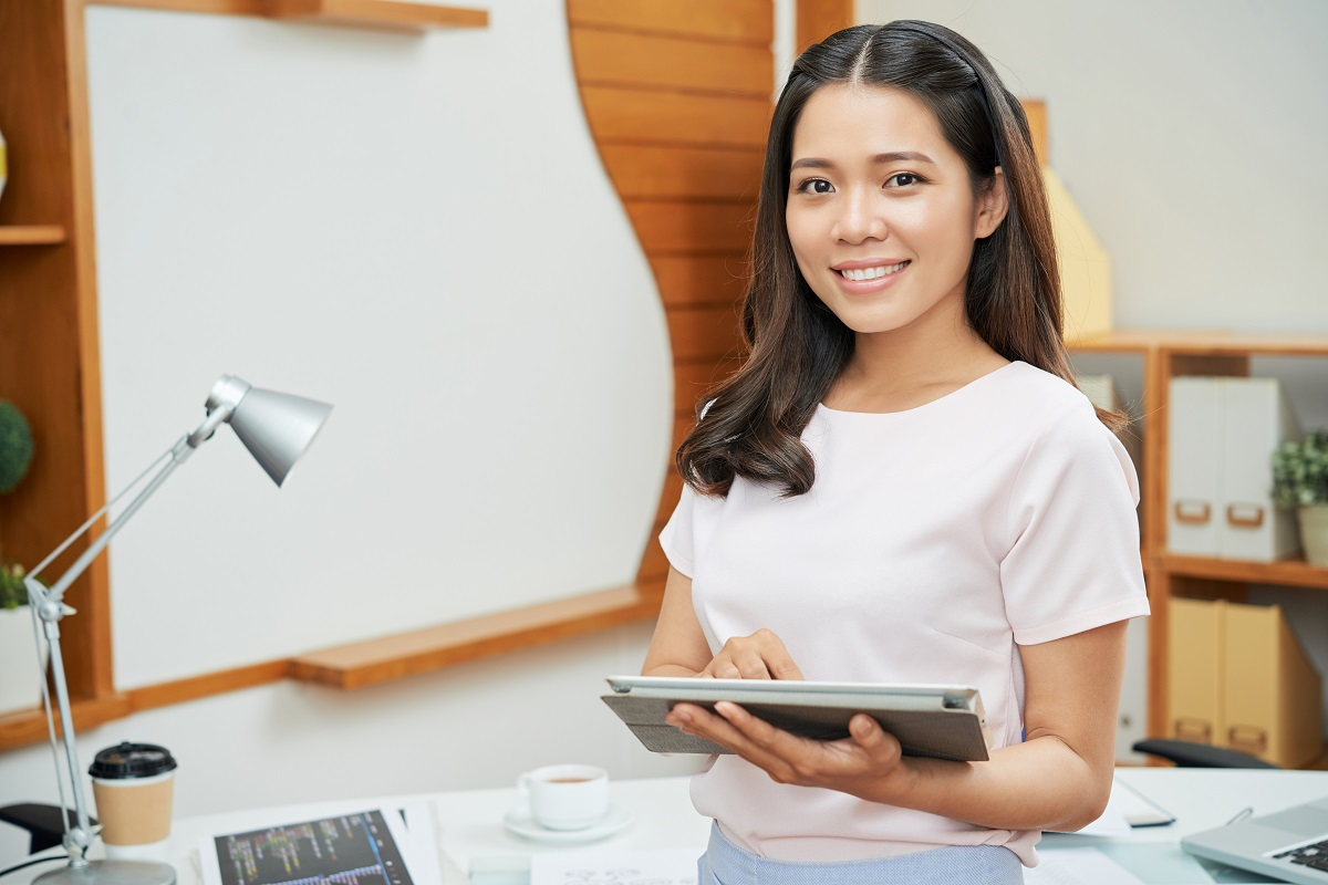 Contemporary businesswoman with tablet smiling at camera