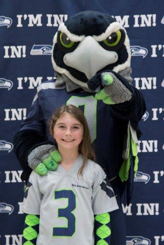 Blitz, the Seahawks mascot, and a little girl.