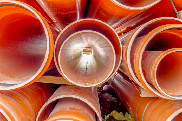 PVC tubes are stacked in a pile at building site,