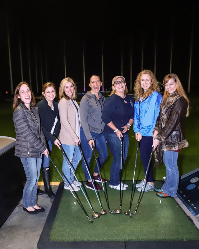 7 women holding golf clubs