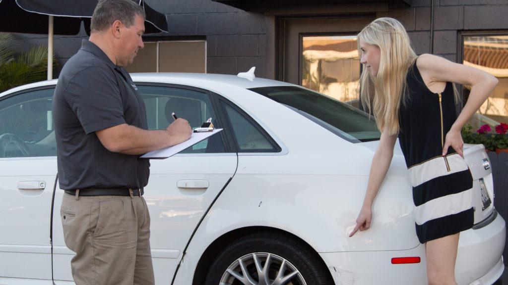 precision auto body employee going through estimate