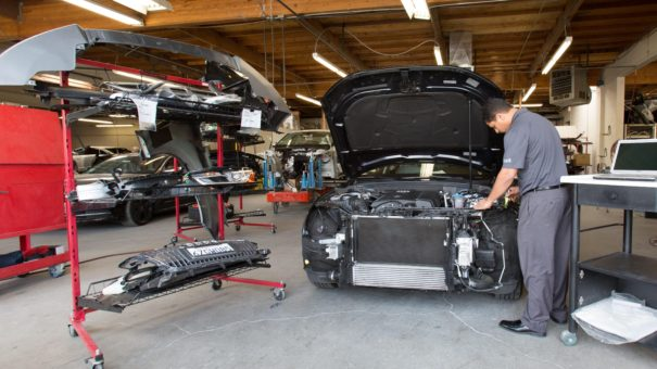 employee disassembling car front bumper and inspecting