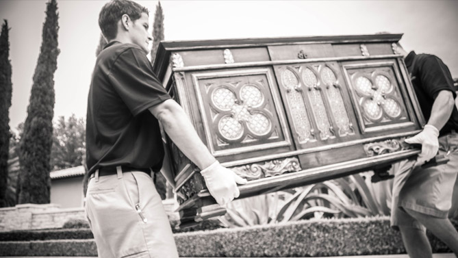 Two WG employees moving an antique chest.
