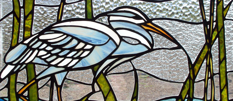 Stained glass crane in moonlight window