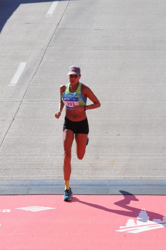 Image of Anita Perez crossing the Chicago Marathon finish line.