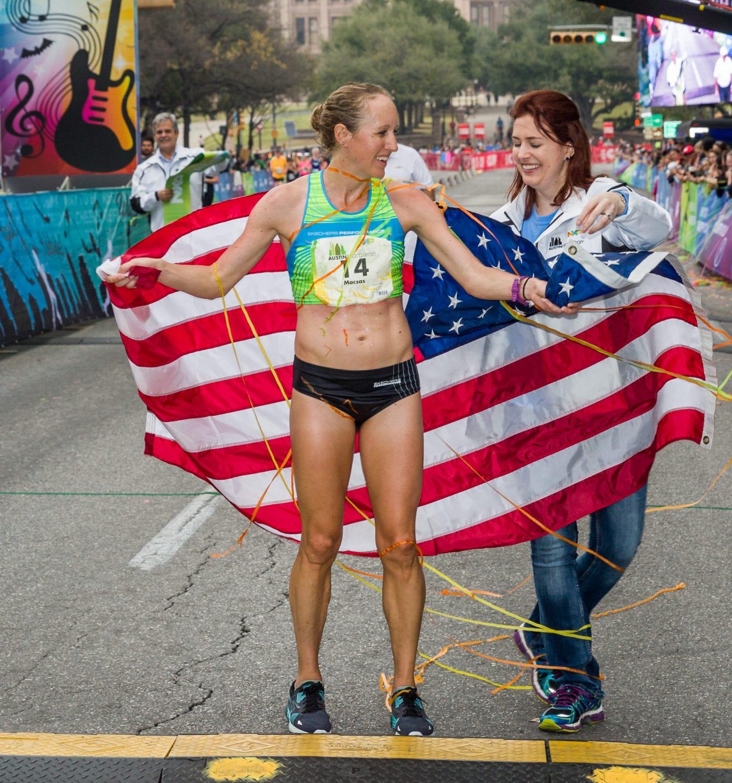 Allison Macsas draped in the American flag after winning the 2017 Austin Marathon.