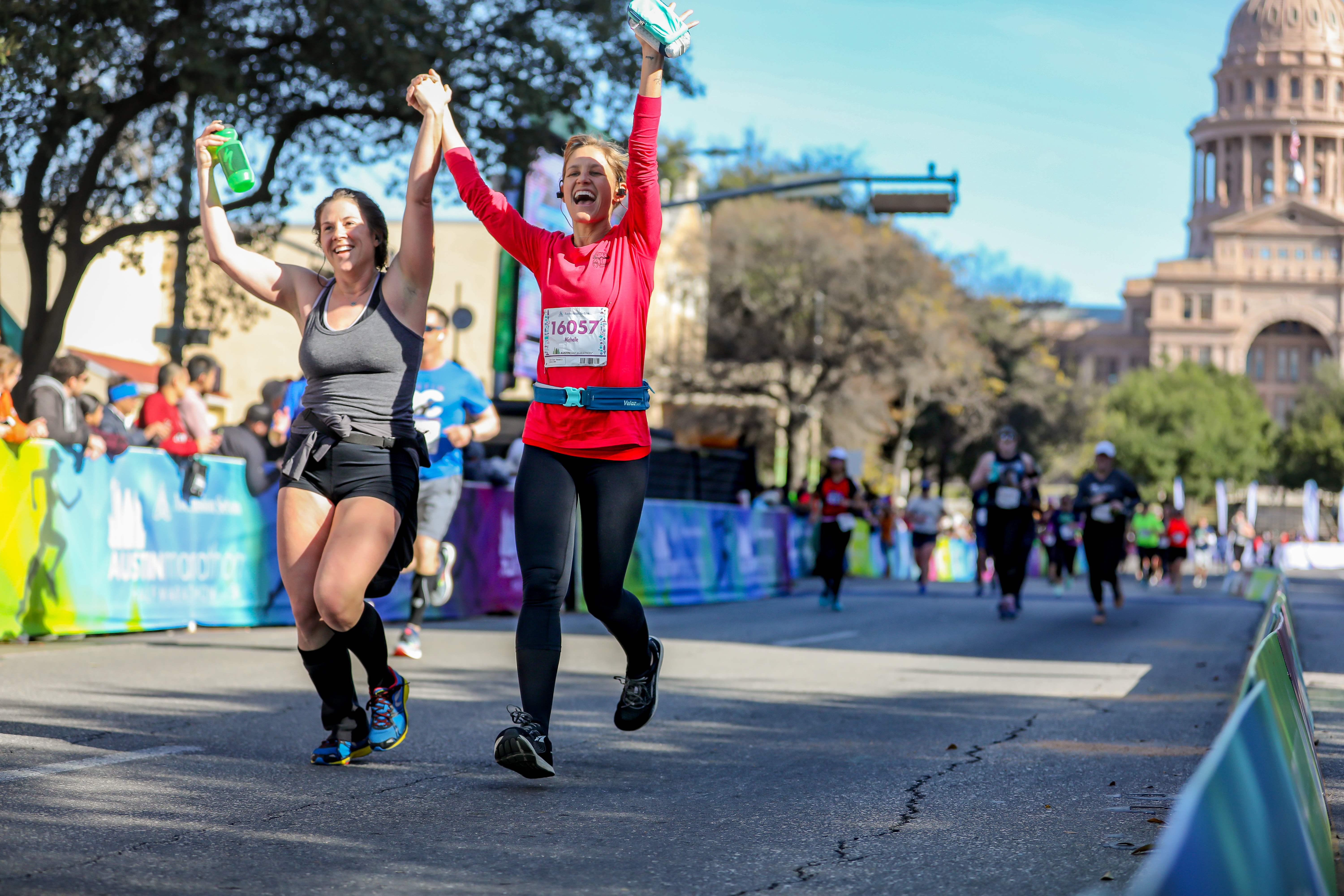 Runners cross the 2019 Austin Marathon finish line and see each other's improvement.