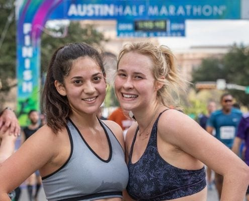 Two female runners pose after completing the 2019 Austin Half Marathon. Follow this free half marathon training plan and you'll cross the 2020 Austin Half Marathon finish line.