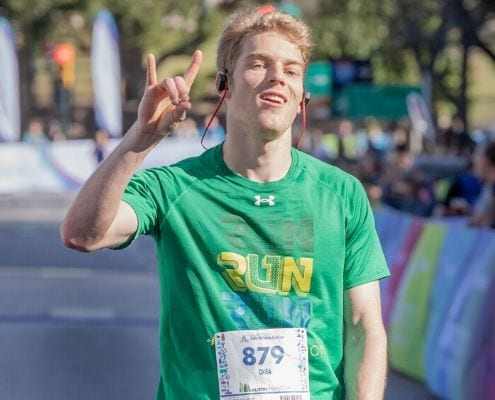 Runner crosses the 2019 Austin Marathon finish line. Download the free marathon training plan and you can cross the 2020 Austin Marathon finish line!