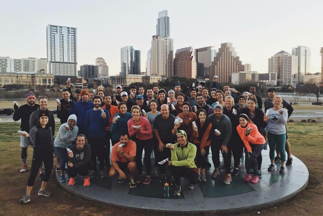 Image of group of runners posing in front of the Austin skyline holding Tacodeli tacos. Tacodeli is the Official Taco of the Austin Marathon.