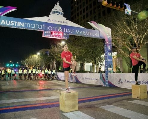 Image of two Camp Gladiator trainers warming up participants of the 2019 Austin Marathon. CG returns as the 2020 Austin Marathon's Official Community Fitness Partner.