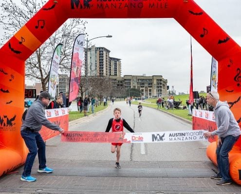 Young runner crosses the finish line of the 2019 Manzano Mile presented by Dole Packaged Foods.
