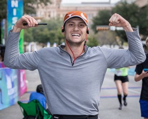 Runner flexes arms while listening to music after he crosses the 2019 Austin Half Marathon finish line. Read this blog and listen to the 10 most recent January running playlist additions.