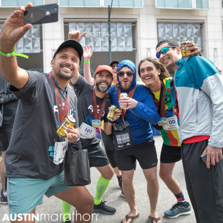 Group of friends take a selfie at the 2019 Austin Marathon finish line, capping off an unforgettable Austin Marathon weekend.