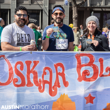 Image of two participants showing off their medals to a friend while they enjoy beers at the Oskar Blues beer garden at the 2019 Austin Marathon, capping off an unforgettable weekend.