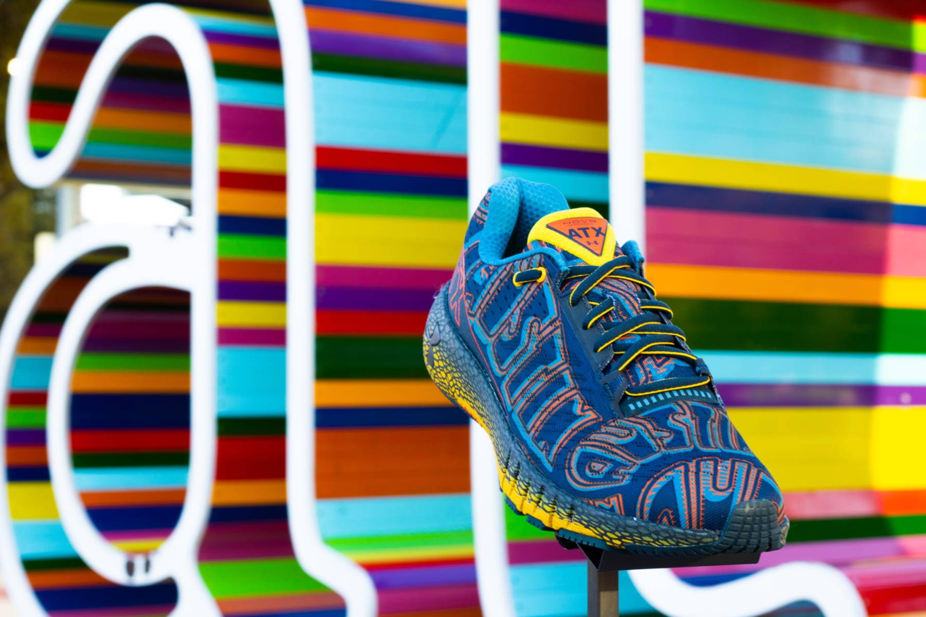 Image of the limited-edition Under Armour HOVR Machina ATX shoe in front of a multi-colored ATX sign. The Austin Marathon is giving away a pair of these shoes every day in April for their 30th Anniversary Giveaway!