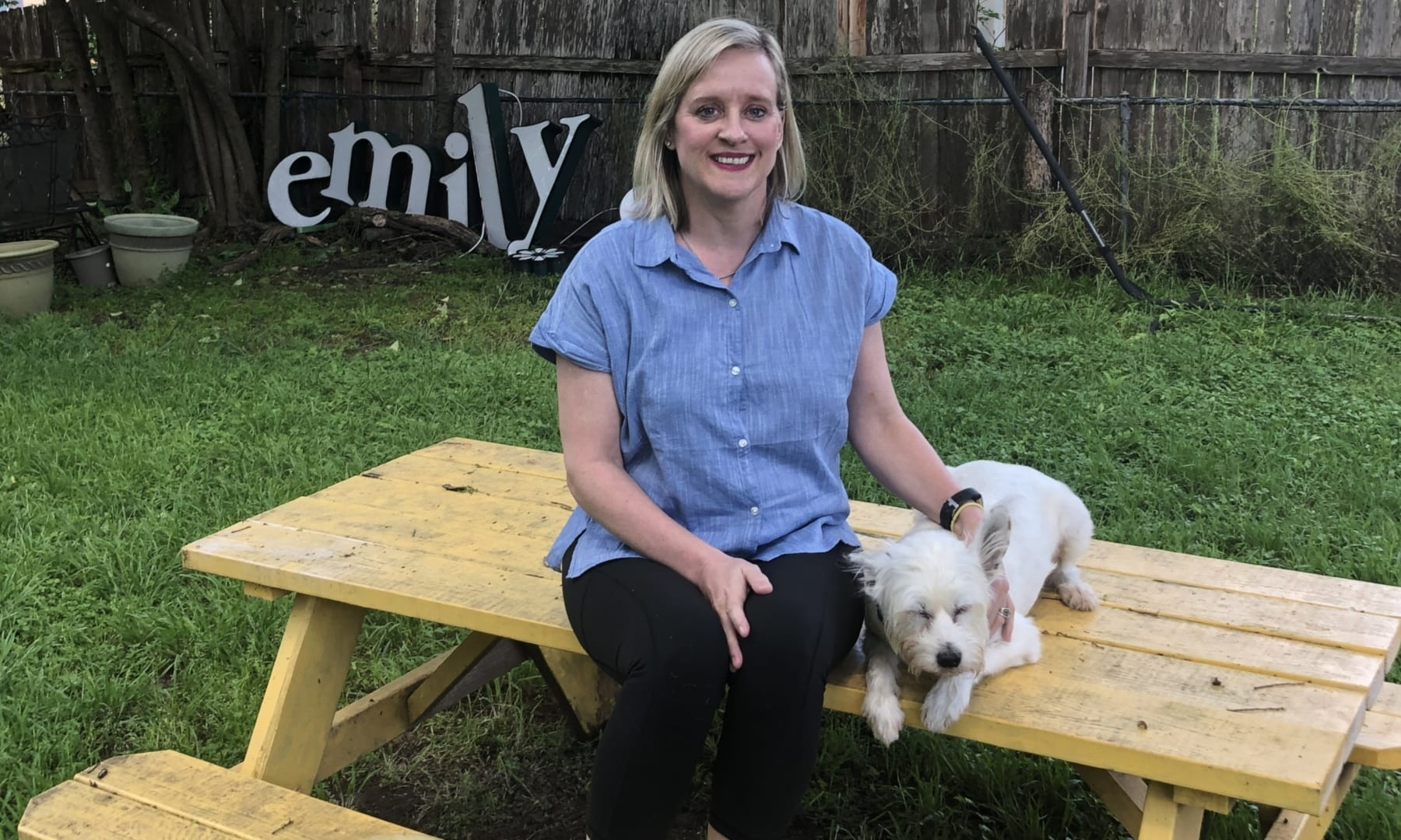 Image of Emily Stevens and one of her dogs sitting on a picnic table.