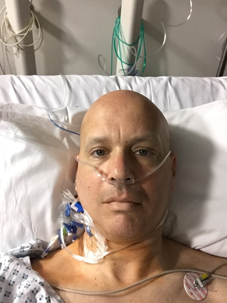 Image of Jonathan Acott in a hospital bed fighting one of his six diagnosed cancers. Read about his journey to run the world and how the Austin Marathon is next!