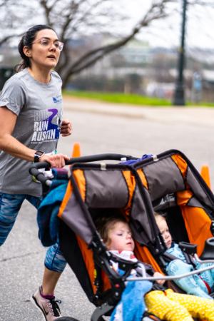 Image of a mother pushing a double-stroller during the 2020 Austin Marathon KXAN SimpleHealth 5K. Thank mom with the downloadable Mother's Day coupon book in this blog!