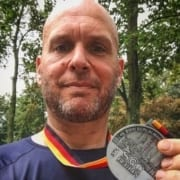 Image of Jonathan Acott showing off his medal from the Berlin Marathon. Read about his journey to run the world and how the Austin Marathon is next!