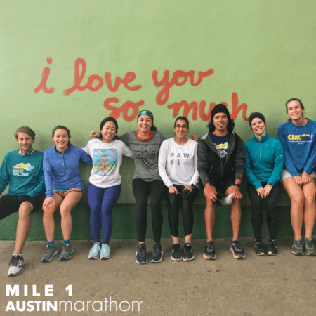 Image of i love you so much mural in Austin with runners from The Morning Jos posing. It's one of the Austin Marathon's favorite on-course murals.