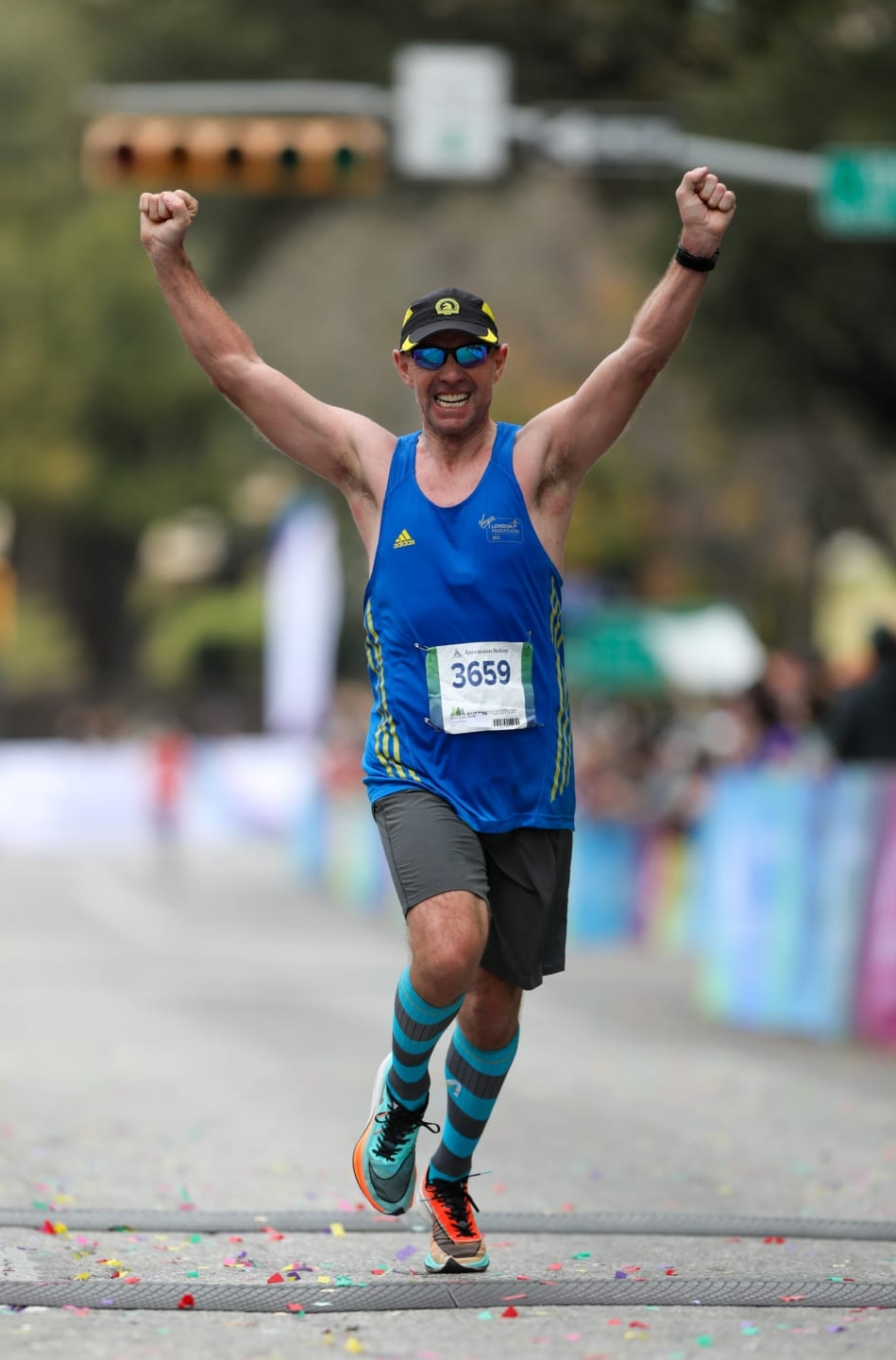 Image of a male runner with his arms raised in triumph crossing the 2020 Ascension Seton Austin Marathon finish line. Credit to Scott Flathouse.