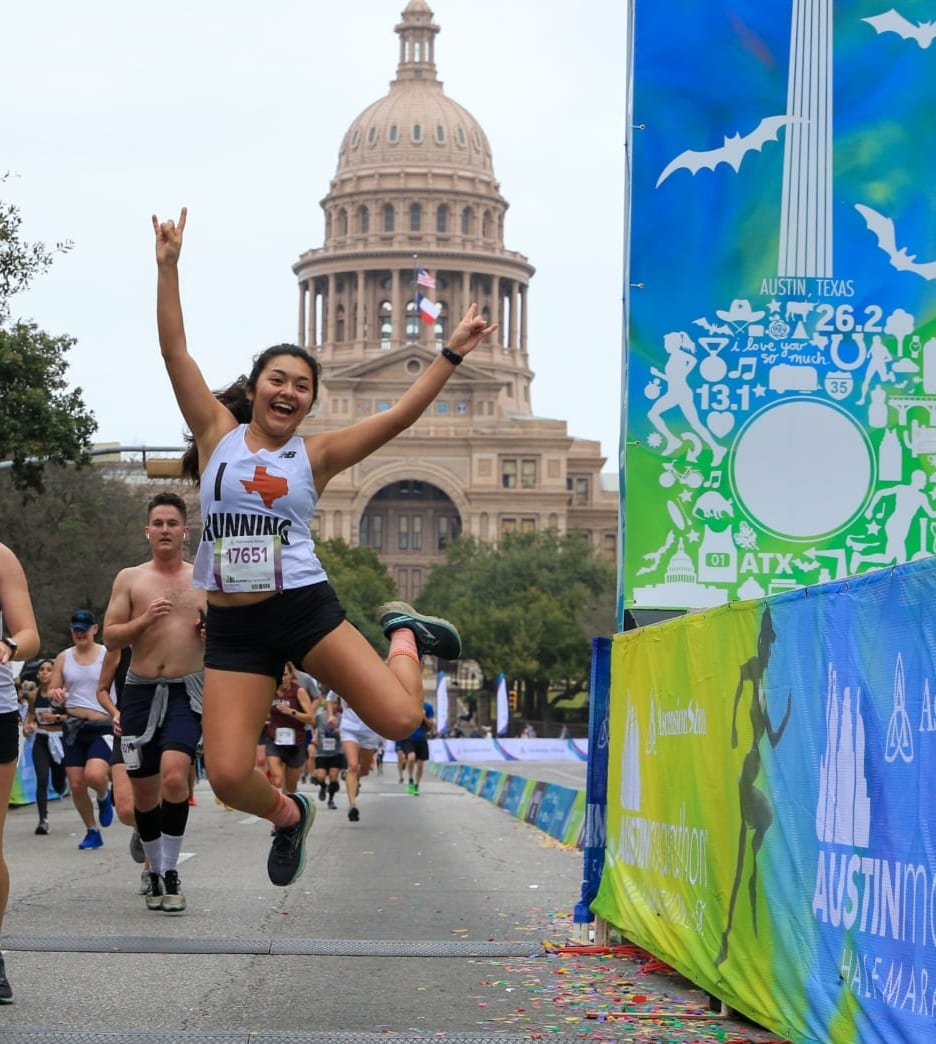 Image of runner jumping while crossing the 2020 Austin Half Marathon finish line. She's in mid-air making the Longhorn sign with both hands. Read this blog and learn how to gain strength so you can cross the finish line like this!