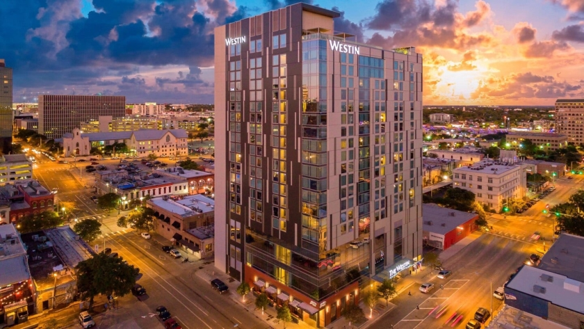 Image of The Westin Austin Downtown hotel with the sunset in the background, credit Westin Austin. Book a luxury hotel and make your Austin Marathon weekend that much more memorable. More information at https://youraustinmarathon.com/austin-luxury-hotels/
