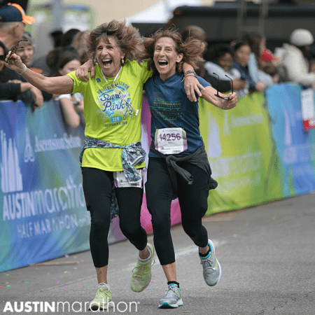Two women embrace as they finish half marathonn in Austin Texas