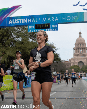 Female runner smiles as she crosses the 2020 Austin Half Marathon finish line.