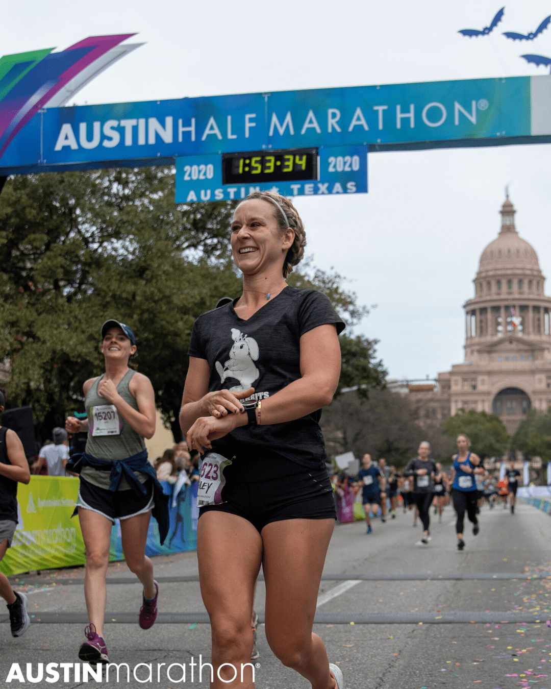 Female runner smiles as she crosses the 2020 Austin Half Marathon finish line.