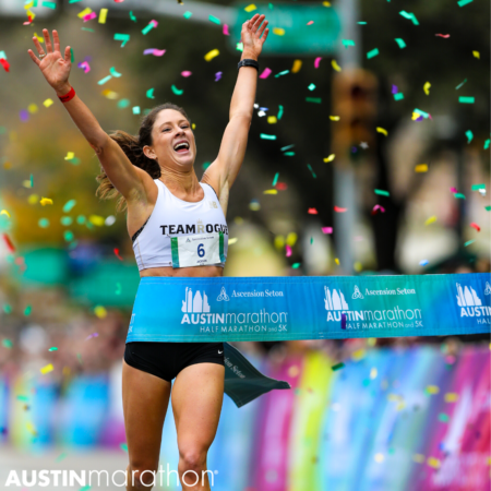 Sarah Jackson, 2020 Austin Marathon female champ, crossing the finish line with her arms raised joyously in the air. Running is a great way to reduce your stress.