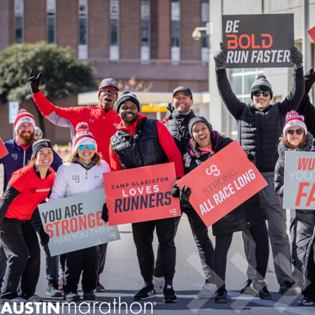 Group of Camp Gladiator coaches cheer for runners and hold signs. They were one of many local businesses to sponsor aid stations at a previous Austin Marathon. Learn more at https://youraustinmarathon.com/sponsor-aid-stations/