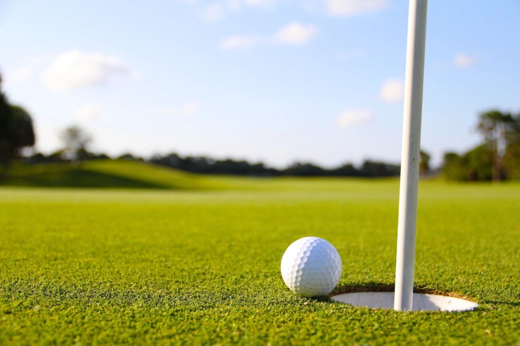 golf ball next to golf flage pole on putting green