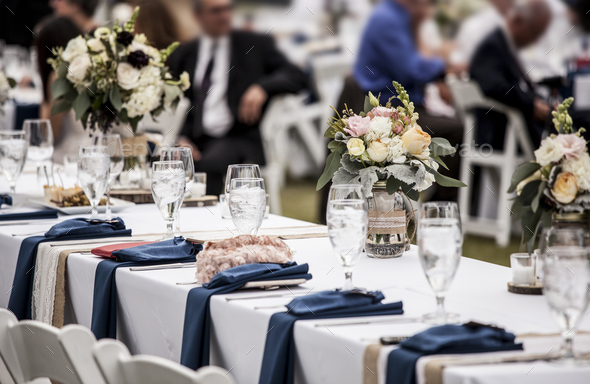 Table set up for wedding reception with people out of focus in background.