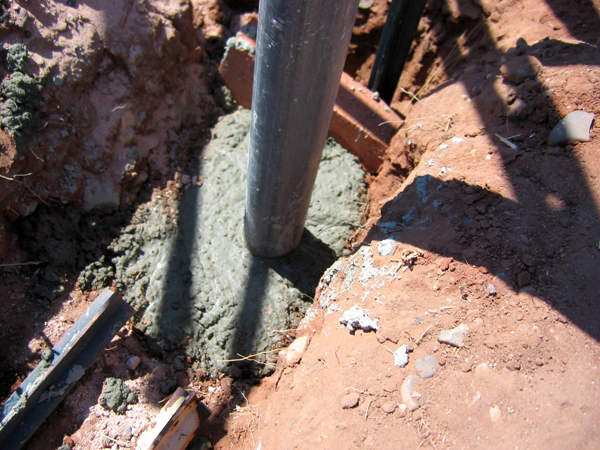 Concrete being poured around gate post