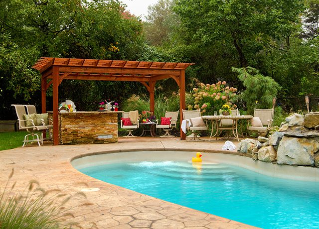 Wooden pergola with an inground pool and a yellow duck