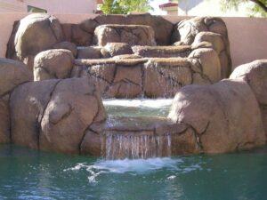 custom rock waterfall in a swimming pool