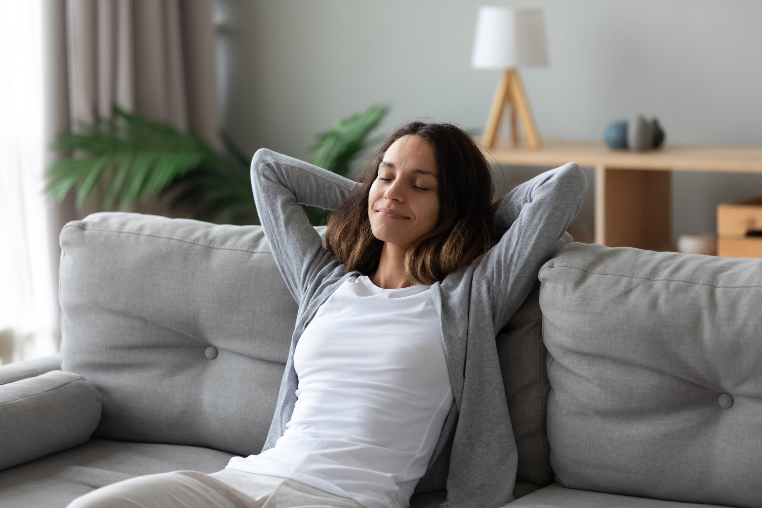 Tranquil smiling biracial millennial woman leaning on sofa, enjoying stress free weekend time at home. Mindful happy mixed race young girl relaxing in living room, meditating, visualizing future.