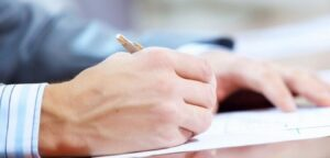 Close-up of person signing a piece of paper