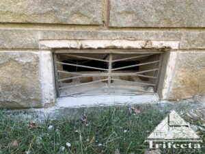 Bedford stone home foundation vent during vent guard installation process