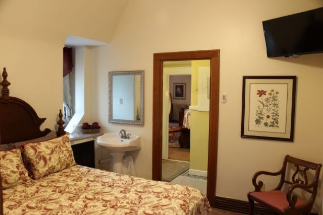 A picture of JC's Room looking across the bed toward the sink and the open bathroom door