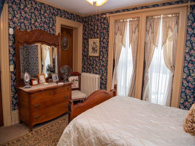 Mary's Room looking from bathroom door across antique Queen bed and toward antique dresser