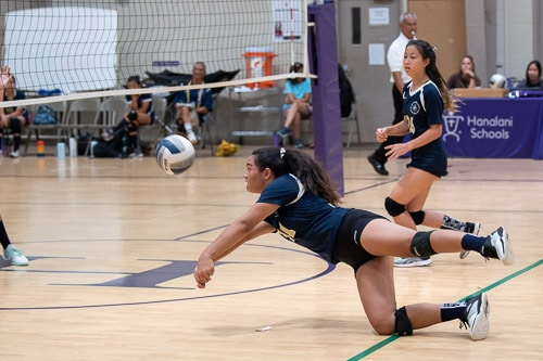Girls volleyball player dives for the ball